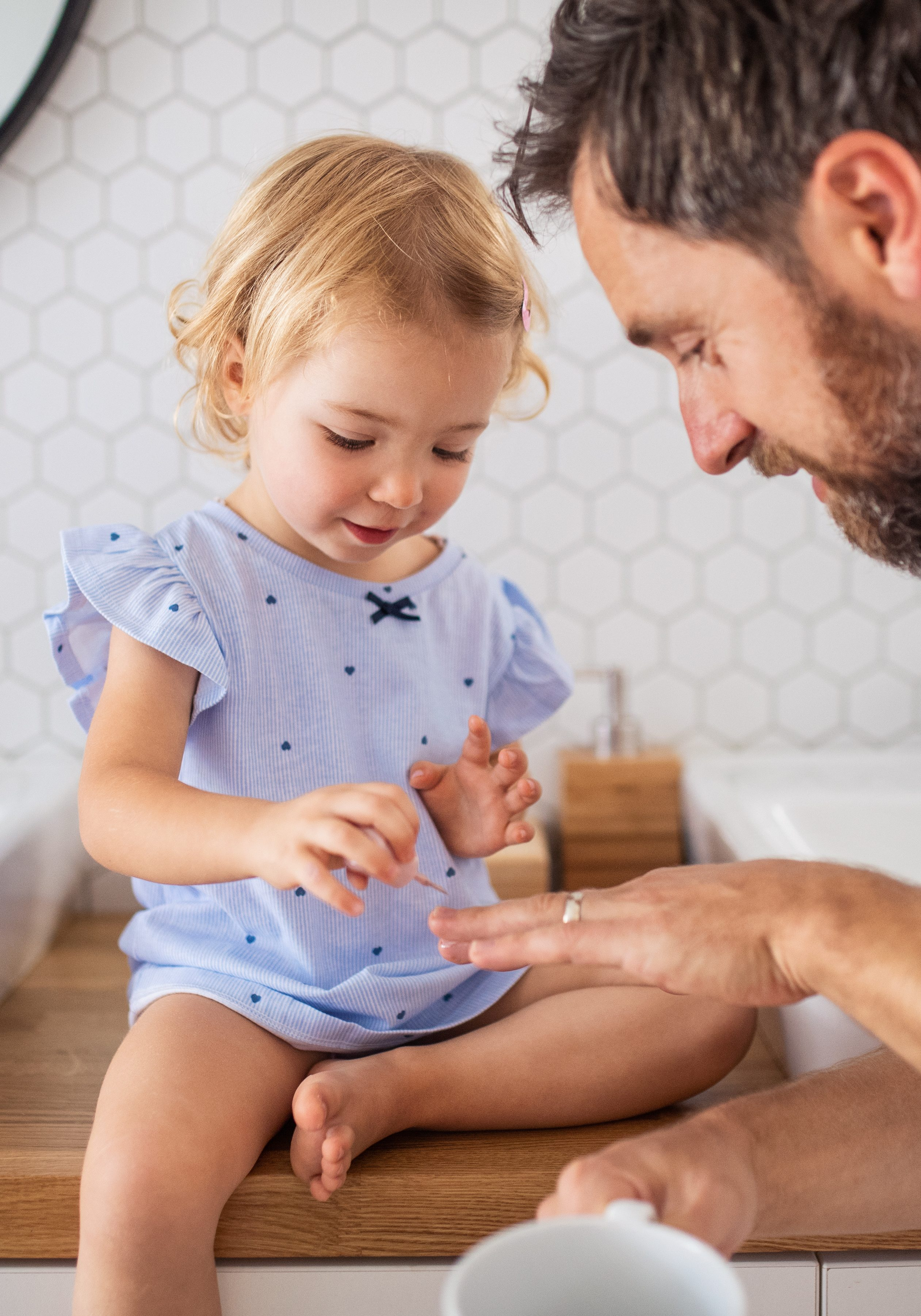 Mature father with small girl indoors in bathroom | Masters And Petersens Flooring